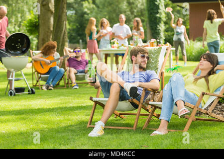 Young friends having barbecue picnic in the nature, playing guitar, playing badminton, enjoying sunny summer day outdoor - Stock Photo