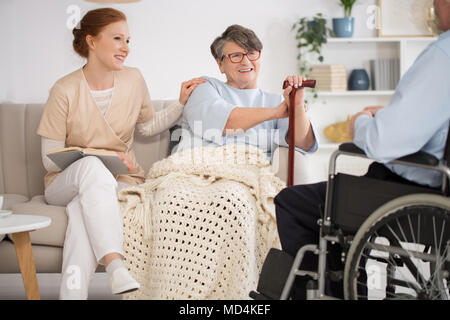 Beautiful nurse spending time with a disabled senior couple in a nursing home - Stock Photo