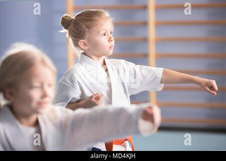 Young girl in kimono exercising during an extra-curricular karate class - Stock Photo