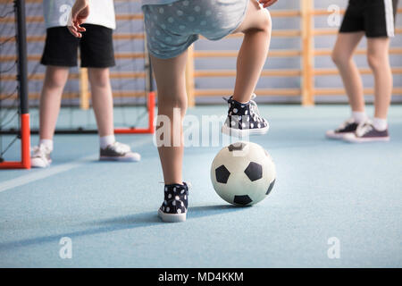 Close-up of boys' legs wearing sneakers while playing football in the playground - Stock Photo