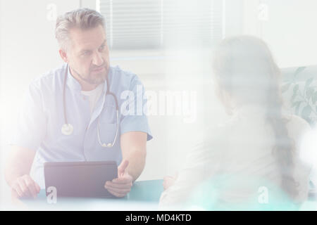 Serious doctor discussing a disease with his patient in hospital