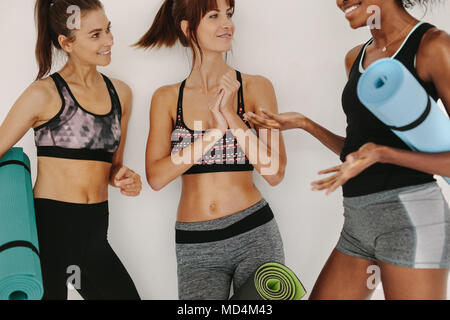 Sporty women relaxing and talking after yoga class in gym. Multiracial female friends in sportswear resting after workout in fitness studio. - Stock Photo