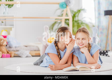 Mischievous twin sisters whispering secrets, lying on a white rug in a cozy children's bedroom - Stock Photo