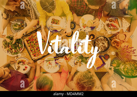 Healthy, vegan food on a table with group of people eating it. Photo with vitality banner - Stock Photo