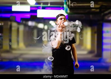 Man in cap smoke an electronic cigarette performing various kind of vaping tricks - Stock Photo