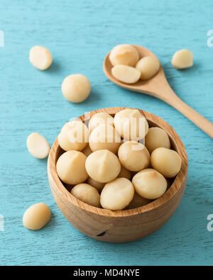 Macadamia nuts in bowl on blue wooden table - Stock Photo
