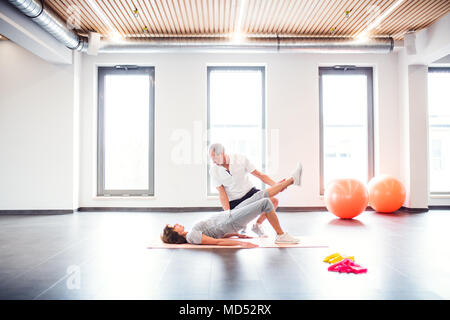 Senior physiotherapist working with a female patient. - Stock Photo