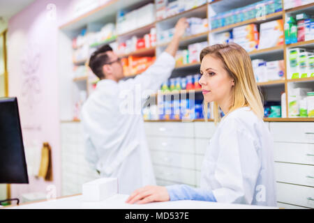 Two pharmacists working in a drugstore. - Stock Photo