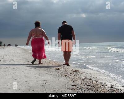 A woman and man walking along the shoreline at Indian Rocks Beach, Florida, USA 2017, © Katharine Andriotis - Stock Photo