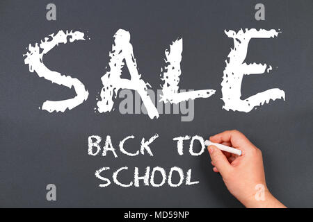 hand writing by white chalk on a blackboard. Back to school sale - Stock Photo
