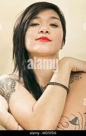 A portrait of a young Japanese woman who has some unidentifiable tattoos. - Stock Photo