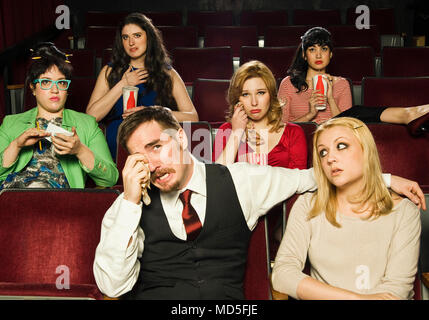 A group of people reacting to a movie in a movie theater. - Stock Photo