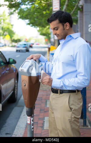 Closeup portrait, young man putting coins in parking meter outside to prevent fines, isolated roads, car, trees background. - Stock Photo