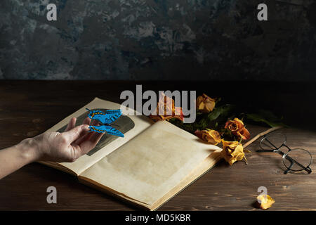 Still life book on the table with flowers and glasses. Butterfly in the hand of the girl.  place for text