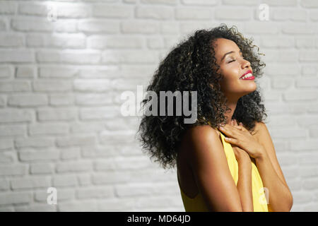 Portrait of happy latina woman smiling and saying prayer. Black girl looking up while praying. - Stock Photo