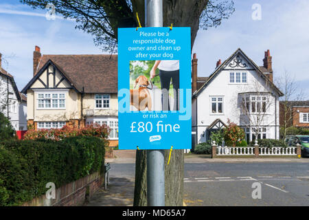 A sign in a suburban street warns people of an £80 fine for failing to clean up after their dog. - Stock Photo