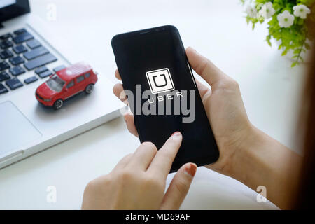 CHIANG MAI,THAILAND - FEB 18, 2018 : A woman hand holding Uber app showing on new mobile Samsung galaxy S8 plus on workspace, Uber is smartphone app-b - Stock Photo