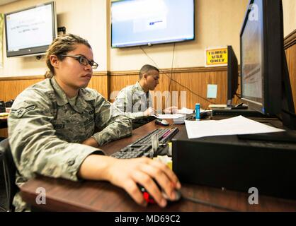 Airman 1st Class Aleigha Rivera, 92nd Air Refueling Squadron squadron aviation resource management journeyman, and Staff Sgt. Jonathan Rivera, 93rd ARS SARM NCO in charge, generate flight authorizations during Red Flag 18-2 at Nellis Air Force Base, Nevada, March 19, 2018. Red Flag gives Airmen an opportunity to experience realistic combat scenarios to prepare and train them for future conflicts. (U.S. Air Force photo illustration/Senior Airman Janelle Patiño) - Stock Photo