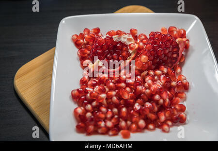 Delicious pomegranate seeds placed in glass jar with fresh organic pomegranates on rustic wooden background.Close up,Copy space - Stock Photo