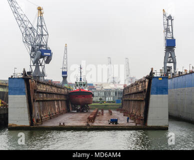 Rotterdam, Netherlands - 20 July 2015: a vessel inside the lifted dry dock of a shipyard at Europort Rotterdam. - Stock Photo