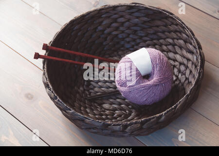 Wool yarn and knitting needles in the basket on the wooden background - Stock Photo