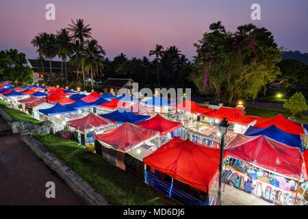 Many lit market stalls at the night market in Luang Prabang, Laos, viewed from above at dusk. - Stock Photo