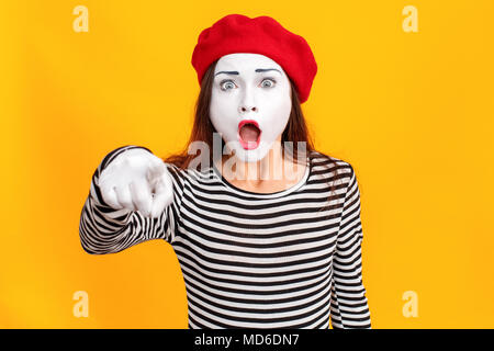 Closeup portrait of amazement mime woman pointing finger at camera. Emotions and feelings concept. Indoor shot, yellow background - Stock Photo