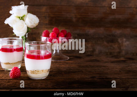 Raspberry dessert from whipped white chocolate mousse, raspberry puree as jelly, and base from almond cookies, rustic wooden background - Stock Photo