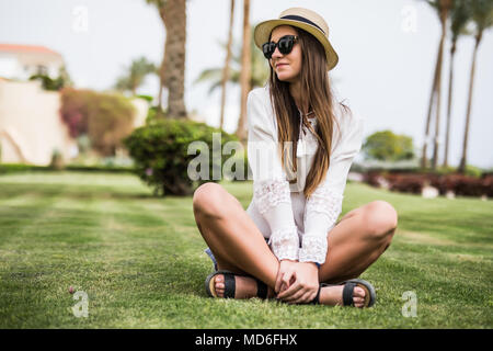 Young beauty woman in sunglasses and straw hat sitiing on grass under palm tree at beach - Stock Photo
