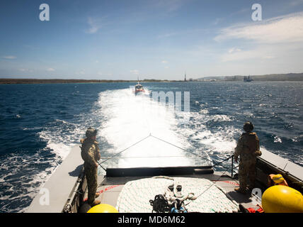 Sailors assigned to Coastal Riverine Squadron (CRS) 4, Det. Guam watch as their Mark VI patrol boat tows a 47-foot Motor Lifeboat assigned to U.S. Coast Guard Sector Guam during a towing exercise in Apra Harbor, Guam, March 28, 2018. CRS-4, Det. Guam is assigned to Commander, Task Force 75, the primary expeditionary task force responsible for planning and execution of coastal riverine operations, explosive ordnance disposal, diving engineering and construction, and underwater construction in the U.S. 7th Fleet area of operations. (U.S. Navy Combat Camera photo by Mass Communication Specialist  - Stock Photo