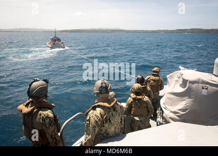 Sailors assigned to Coastal Riverine Squadron (CRS) 4, Det. Guam watch as their Mark VI patrol boat is towed by a 47-foot Motor Lifeboat, assigned to U.S. Coast Guard Sector Guam, during a towing exercise in Apra Harbor, Guam, March 28, 2018. CRS-4, Det. Guam is assigned to Commander, Task Force 75, the primary expeditionary task force responsible for planning and execution of coastal riverine operations, explosive ordnance disposal, diving engineering and construction, and underwater construction in the U.S. 7th Fleet area of operations. (U.S. Navy Combat Camera photo by Mass Communication Sp - Stock Photo