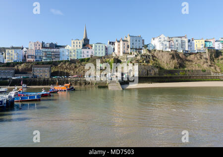 Fishing boats and leisure boats moored at low tide in Tenby Harbour in Pembrokeshire, Wales - Stock Photo