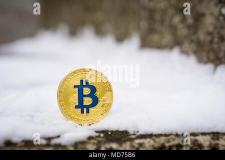 A gold colored Bitcoin placed in snow on concrete. Isolated scene of  cryptocurrency in snow - Stock Photo