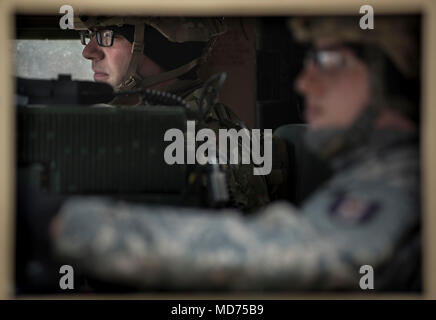 Sgt. Jason Evans (left) and Spc. John Hare, U.S. Army Reserve military police Soldiers with the 94th Military Police Company, out of Londonderry, New Hampshire, prepare for a live fire range during Operation Cold Steel at Fort McCoy, Wisconsin, March 26, 2018.  This iteration of Cold Steel is called Task Force Triad, a mounted gunnery training exercise in which Soldiers work as truck teams to quailfy on live-fire driving lanes. Task Force Triad runs from February to May. Each team who trains here completes a 14-day cycle that includes primary marksmanship training, a gunner skill test, digital - Stock Photo