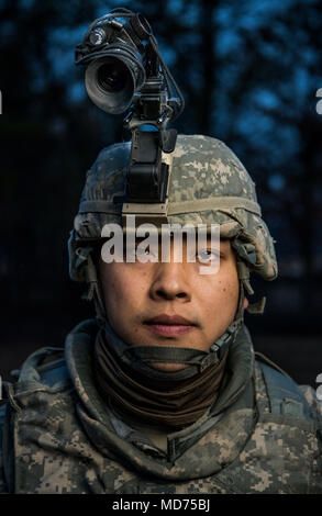 Spc. Fei Lin, a U.S. Army Reserve military police with the 94th Military Police Company, out of Londonderry, New Hampshire poses for a portrait during Operation Cold Steel at Fort McCoy, Wisconsin, March 26, 2018.  This iteration of Cold Steel is called Task Force Triad, a mounted gunnery training exercise in which Soldiers work as truck teams to quailfy on live-fire driving lanes. Task Force Triad runs from February to May. Each team who trains here completes a 14-day cycle that includes primary marksmanship training, a gunner skill test, digital simulated gunnery, ground qualification and fi - Stock Photo