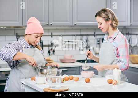 Professional female confectioners whisking eggs and sifting flour through sieve while making cake in modern kitchen - Stock Photo