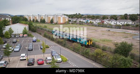 Class 150 diesel train on Arriva Trains Wales service to Bridgend passing car park of Cardiff University north of Cathays station - Stock Photo