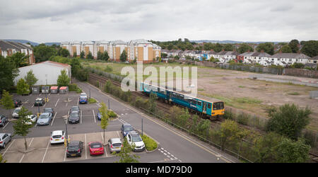 Class 143 diesel train on Arriva Trains Wales service to Barry Island passing car park of Cardiff University north of Cathays station - Stock Photo