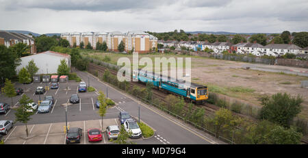 Class 142 diesel train on Arriva Trains Wales service to Barry Island passing car park of Cardiff University north of Cathays station - Stock Photo
