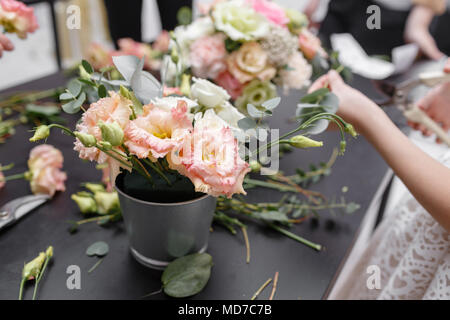 Master class on making bouquets for kids. Spring bouquet in metal ornamental flowerpot. Learning flower arranging, making beautiful bouquets with your own hands - Stock Photo