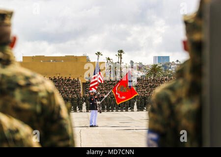 The U.S. Marine Corps Color Guard presents the National Colors for the playing of the National Anthem during a West Coast tour performance at Marine Corps Recruit Depot (MCRD), San Diego, Ca., March 17, 2018. The audince members of the ceremony included many current recruits as well as drill instructors of MCRD San Diego.(Official Marine Corps photo by Cpl. Damon Mclean/Released) - Stock Photo