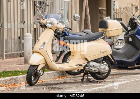 Como, Italy - November 4, 2017: A typical Italian Vespa scooter parked in a street in the city center on a fall day - Stock Photo