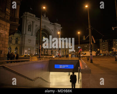 BUDAPEST, HUNGARY - APRIL 6, 2018: Man going down the stairs of a metro Station in front of Budapest Keleti Palyaudvar train station at night  Picture - Stock Photo