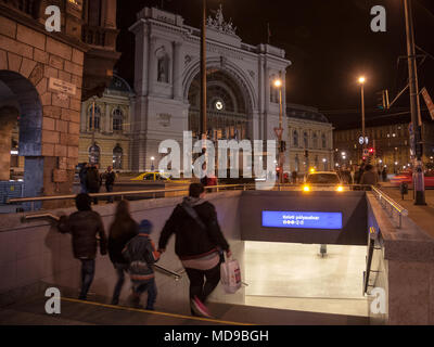 BUDAPEST, HUNGARY - APRIL 6, 2018: Family going down the stairs of a metro Station in front of Budapest Keleti Palyaudvar train station at night  Pict - Stock Photo