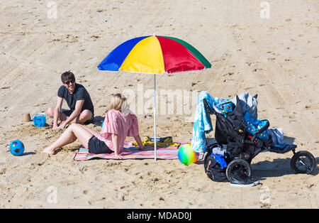 Bournemouth, Dorset, UK. 19th April 2018. UK weather: lovely warm sunny day at Bournemouth beaches with clear blue skies and unbroken sunshine, as visitors head to the seaside to enjoy the warmest day of the year so far. Couple relaxing on the beach under colourful parasol with pushchair buggy by the side. Credit: Carolyn Jenkins/Alamy Live News - Stock Photo