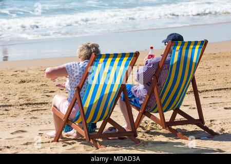 Bournemouth, Dorset, UK. 19th April 2018. UK weather: lovely warm sunny day at Bournemouth beaches with clear blue skies and unbroken sunshine, as visitors head to the seaside to enjoy the warmest day of the year so far. Mature couple relaxing in deckchairs on the beach. Credit: Carolyn Jenkins/Alamy Live News - Stock Photo