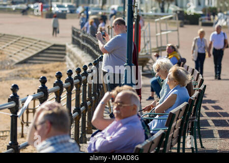 North Wales, UK 19th April 2018, UK Weather:  With a high over the much of the UK its time to enjoy the hottest day of the year so far this year. Visitors to the coastal town of Llandudno enjoying the sunny weather sat the benches along the seafront, Wales - Stock Photo