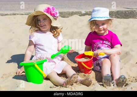 Bournemouth, Dorset, UK. 19th April 2018. UK weather: lovely warm sunny day at Bournemouth beaches with clear blue skies and unbroken sunshine, as visitors head to the seaside to enjoy the warmest day of the year so far. Three year old twins enjoy playing in the sand with their buckets and spades. Credit: Carolyn Jenkins/Alamy Live News - Stock Photo