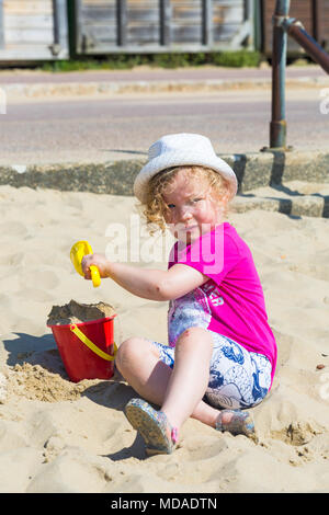 Bournemouth, Dorset, UK. 19th April 2018. UK weather: lovely warm sunny day at Bournemouth beaches with clear blue skies and unbroken sunshine, as visitors head to the seaside to enjoy the warmest day of the year so far. Three year old girl enjoys playing in the sand with her bucket and spade.  Credit: Carolyn Jenkins/Alamy Live News - Stock Photo