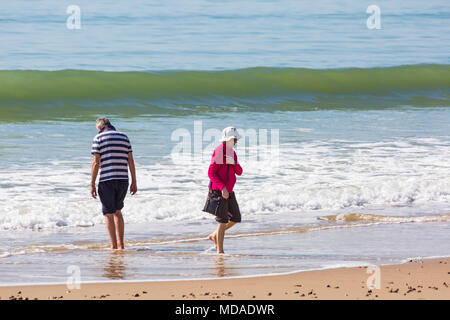 Bournemouth, Dorset, UK. 19th April 2018. UK weather: lovely warm sunny day at Bournemouth beaches with clear blue skies and unbroken sunshine, as visitors head to the seaside to enjoy the warmest day of the year so far. Couple paddling in the sea at Bournemouth beach. Credit: Carolyn Jenkins/Alamy Live News - Stock Photo